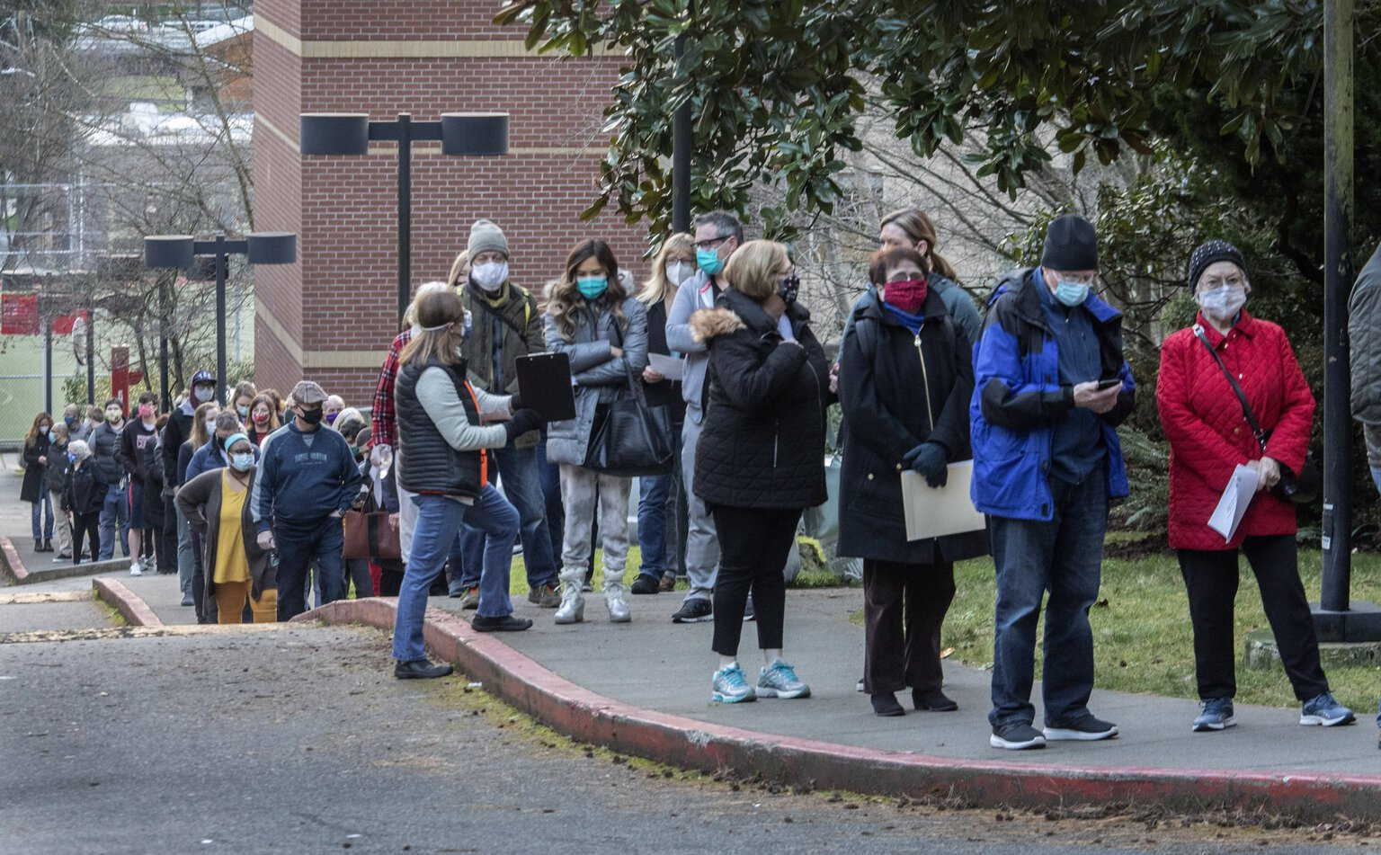 A volunteer walks down the line of people waiting on the Seattle University campus for their COVID-19 vaccinations last month. (Steve Ringman / The Seattle Times)